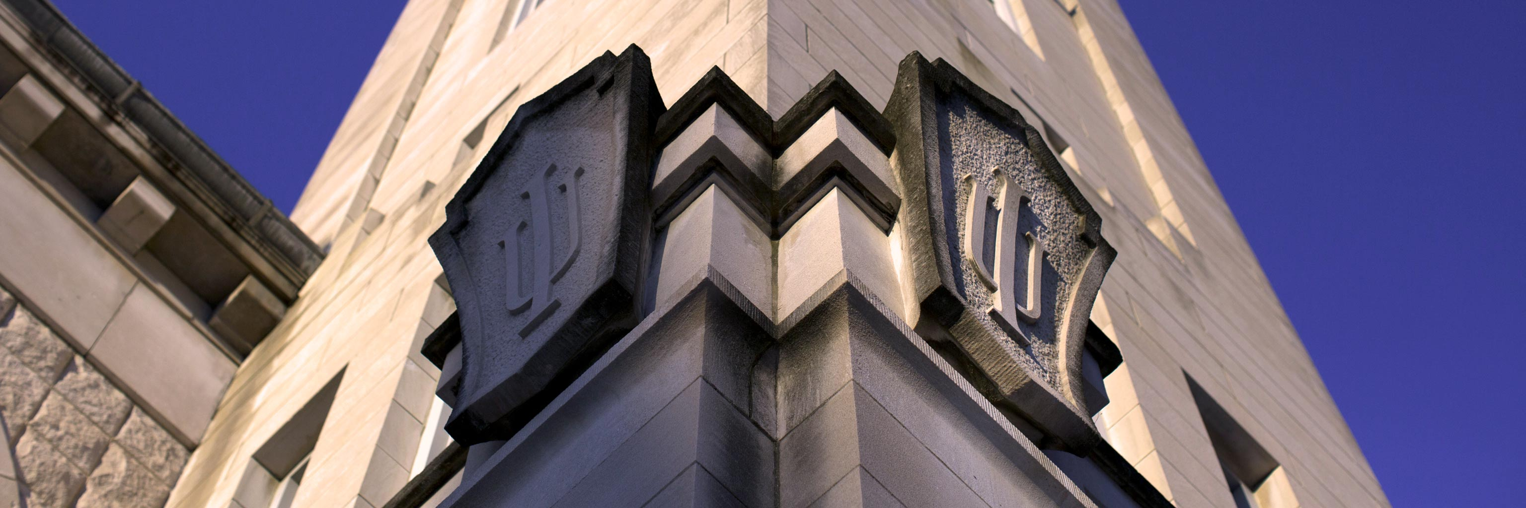 IU trident carved into the exterior of a limestone building