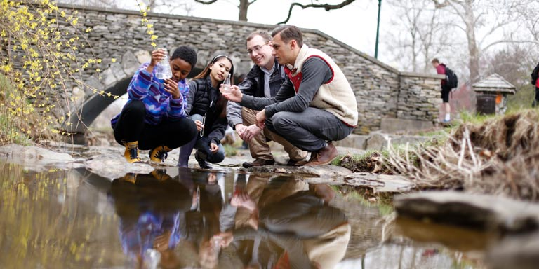 Four students use a beaker to test the water in the Jordan River