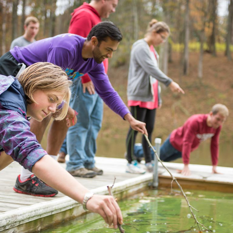 Students using twigs to prod the surface of a lake for research